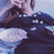 Frau isst Popcorn vor dem Fernseher