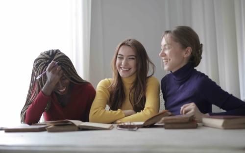 Frauen die zusammensitzen, lernen und lachen